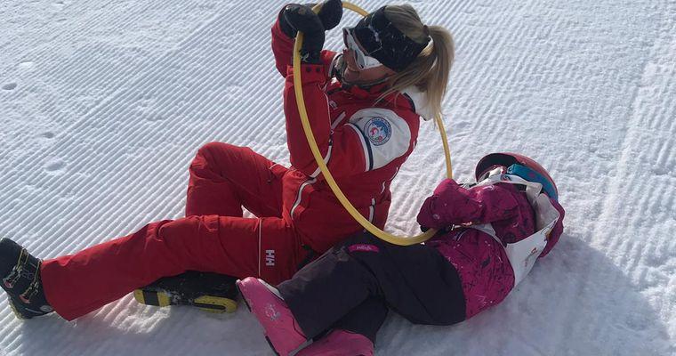 Deux enfants sur les skis avec leur moniteur