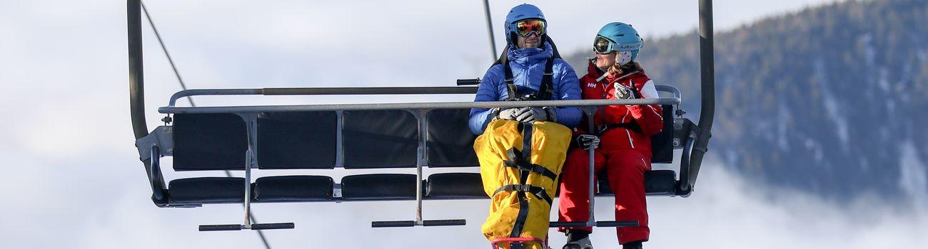 Monitrice et son élève sur un télésiège lors d'une sortie handiski
