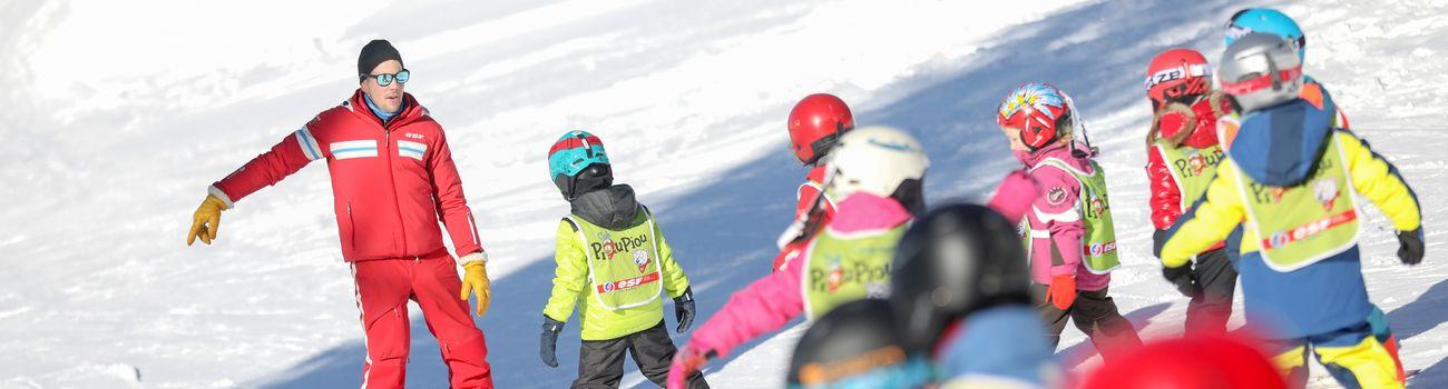 Groupe d'enfants sur les pistes en ski avec leur moniteur