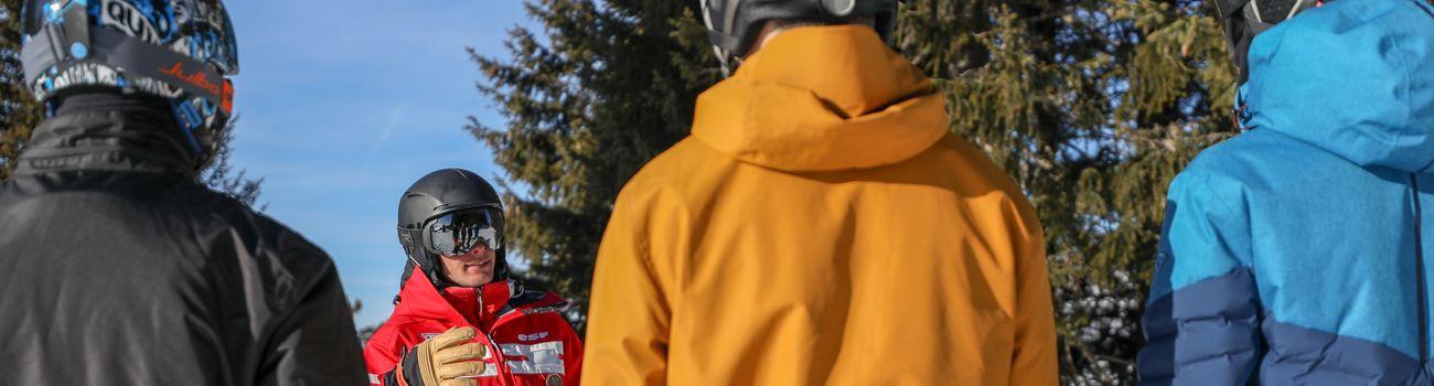 Moniteur donnant des conseils aux ados lors d'un cours de ski