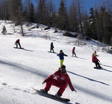 Enfants en Snowboard sur les pistes du domaine Isola 2000