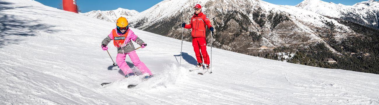 Enfant dérapant en ski sous le regard de son moniteur ESF La Colmiane