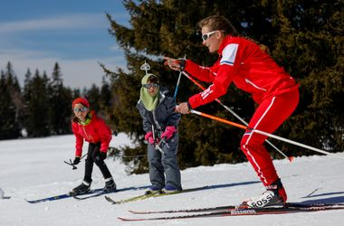 Monitrice donnant des conseils à deux enfants en ski de fond
