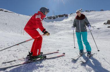Moniteur donnant des conseils en ski à une élève à La Colmiane
