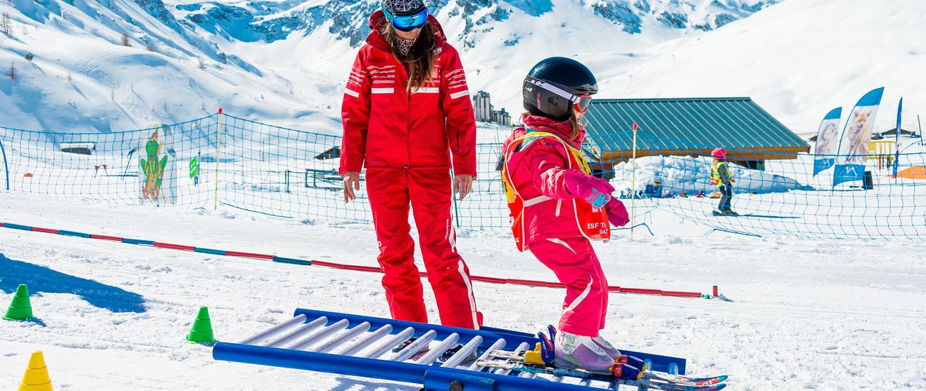 Petite fille en ski dans le club piou piou avec sa monitrice
