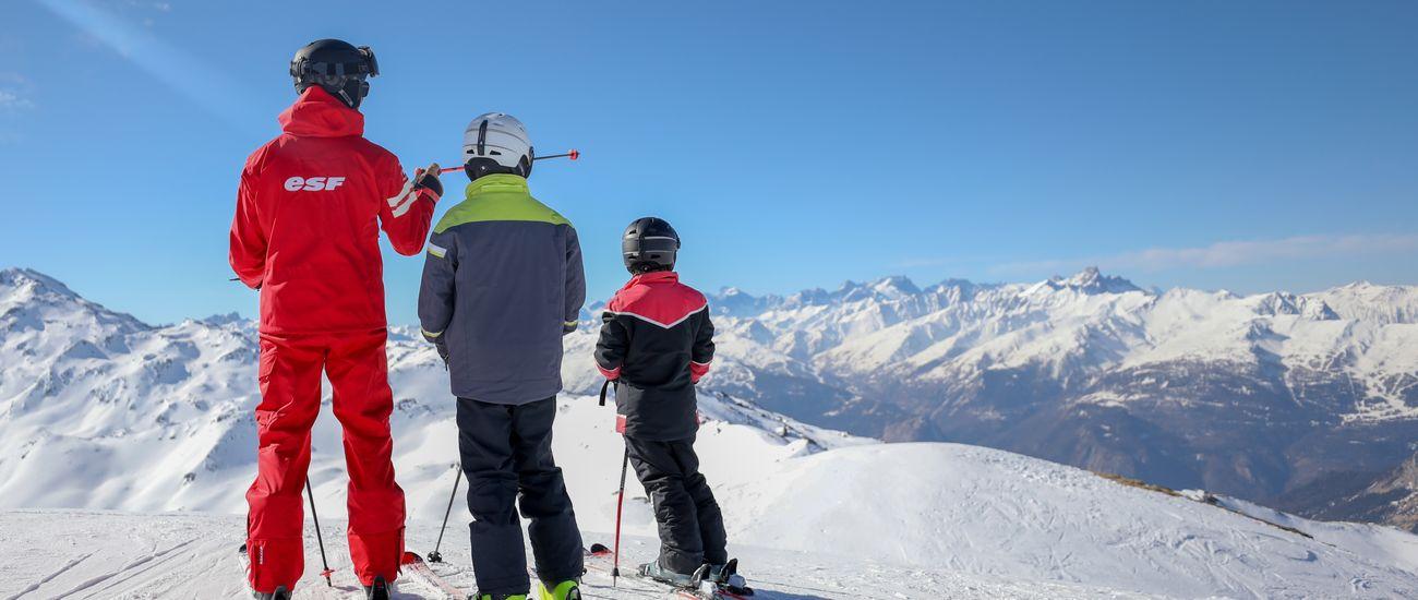 Enfants en leçons particulières de ski à l'écoute de leur moniteur à Tignes Les Brévières