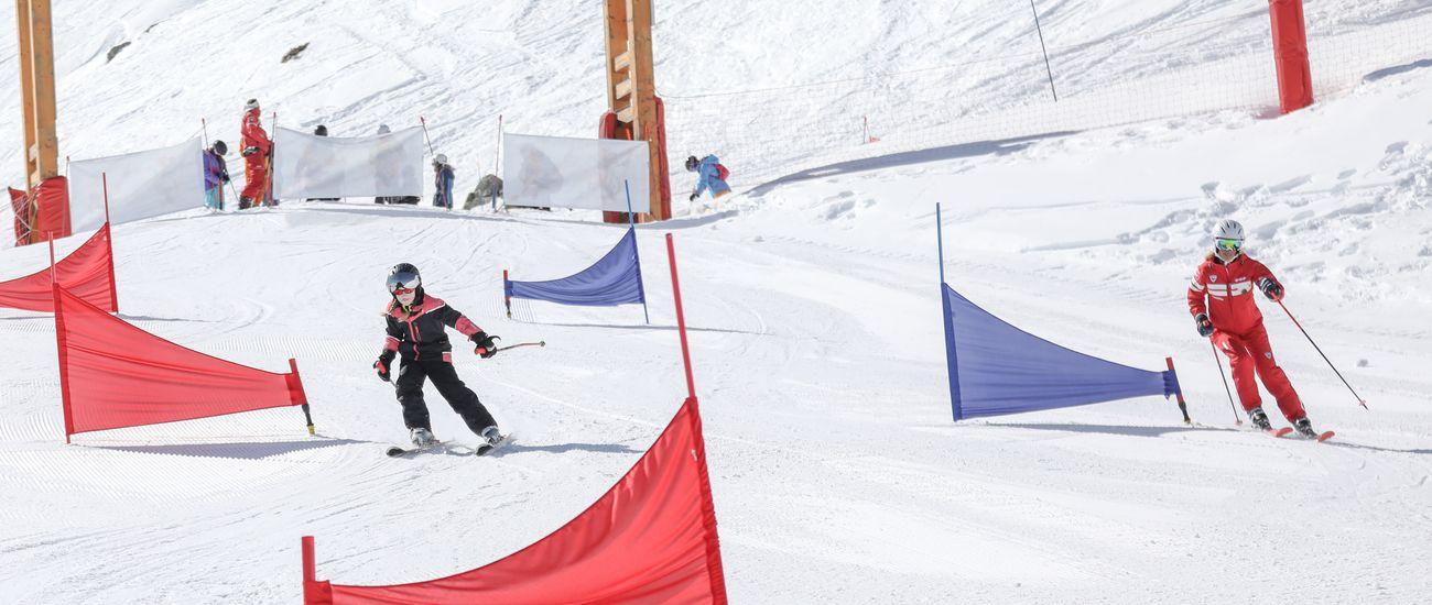 Enfant en compétition de ski avec son moniteur