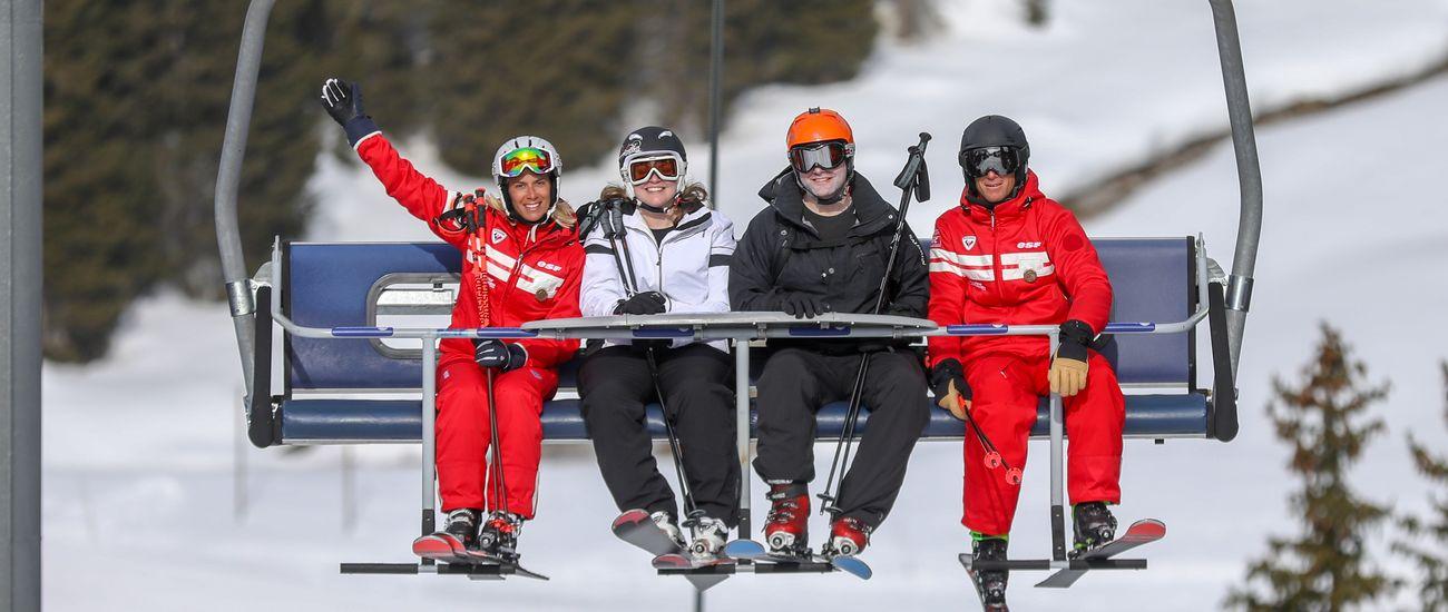 Deux élèves et deux moniteurs sur le télésiège lors de leur cours privé de ski